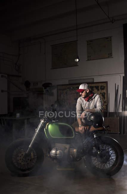 Professional mechanic leaning on custom motorbike at workshop — Stock Photo