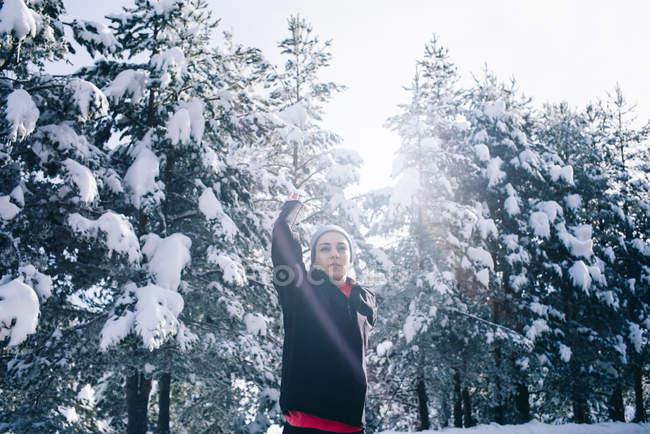 Portrait d'une jeune femme faisant de l'exercice dans une forêt enneigée . — Photo de stock