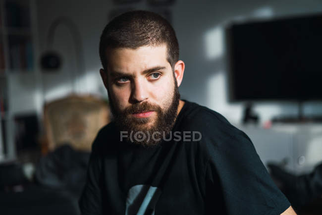 Portrait of thoughtful bearded man looking away at home. — Stock Photo