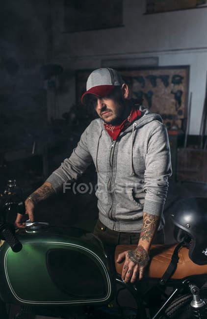 Portrait of man in cap posing with custom motorbike at workshop — Stock Photo