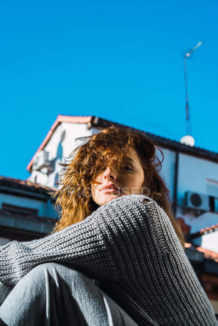 Young woman with curly hair posing on balcony — Stock Photo