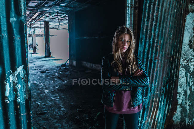 Young woman standing at doorway and posing in grungy old building. — Stock Photo