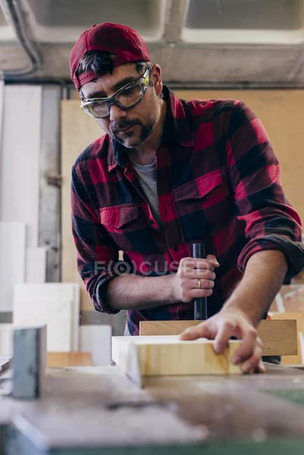 Tischler in Sicherheitsgläsern schneidet Stück Holz in Werkstatt — Stockfoto