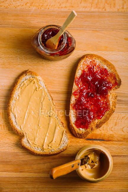 Directamente sobre la vista de mantequilla de maní y jalea bocadillos e ingredientes en la mesa - foto de stock