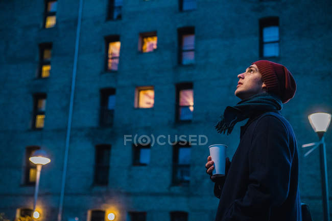 Side view of man walking on street with coffee and looking up — Stock Photo