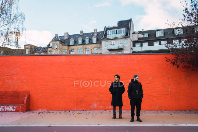Two men in warm clothes standing by orange wall on street scene and looking aside — Stock Photo