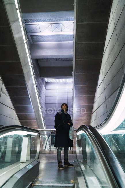 Человек, глядя на движущиеся лестницы проход в торговом центре — стоковое фото