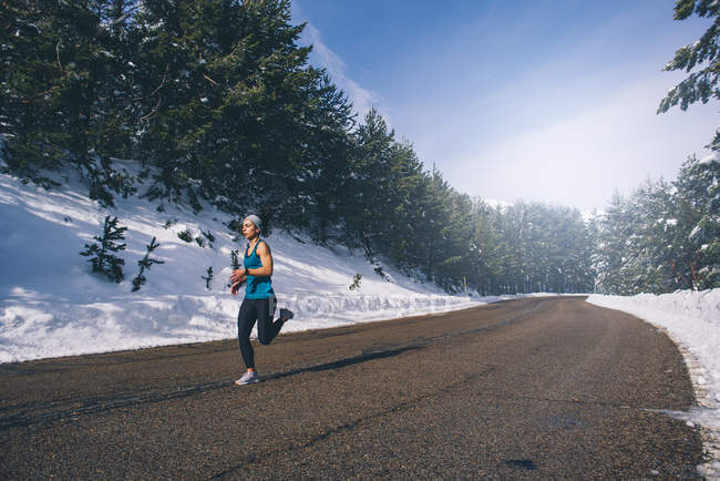 Young fit woman running in snowy area. — Stock Photo