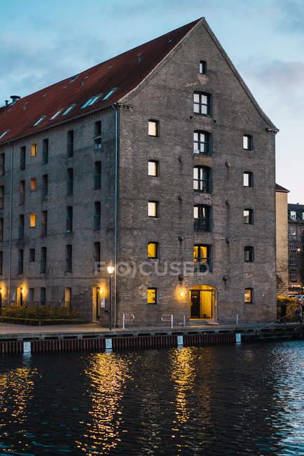 Vista dell'edificio urbano vintage grigio grande alle città lungo il fiume — Foto stock