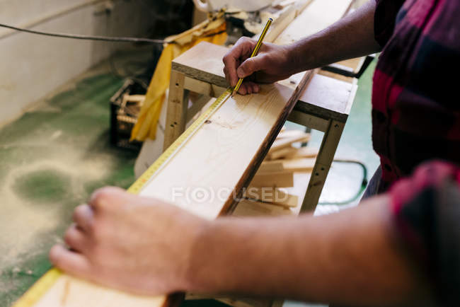 Charpentier récolté mesurant un morceau de bois — Photo de stock
