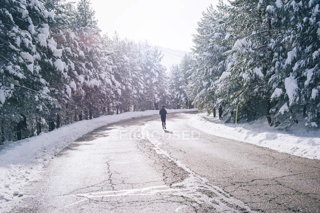 Rear view of woman running on road along snowy woods — Stock Photo