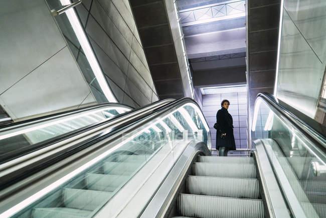 Низкий угол обзора человека, позирующего возле движущихся лестниц на малл — стоковое фото