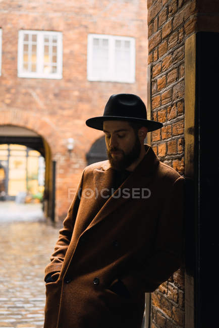 Stylish  man in coat and hat leaning on archway wall and looking down — Stock Photo