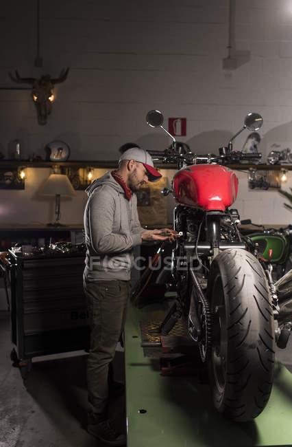 Vista lateral de moto personalizado fijación mecánica en el taller - foto de stock