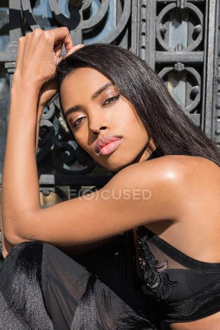 Donna nera alla moda che propone contro il bassorilievo in metallo — Foto stock