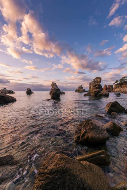 Rocky paesaggio costiero sotto il tramonto cloudscape — Foto stock