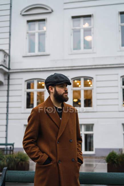 Retrato de hombre barbudo con estilo en abrigo vintage y gorra en posar calle de la ciudad . - foto de stock