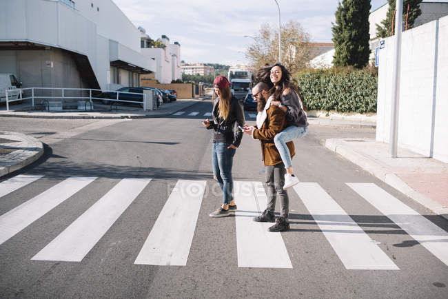 Group of friends at zebra crossing at street scene — Stock Photo