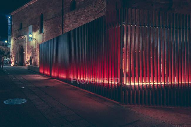Illuminato con recinzione in metallo rosso sulla strada di notte . — Foto stock