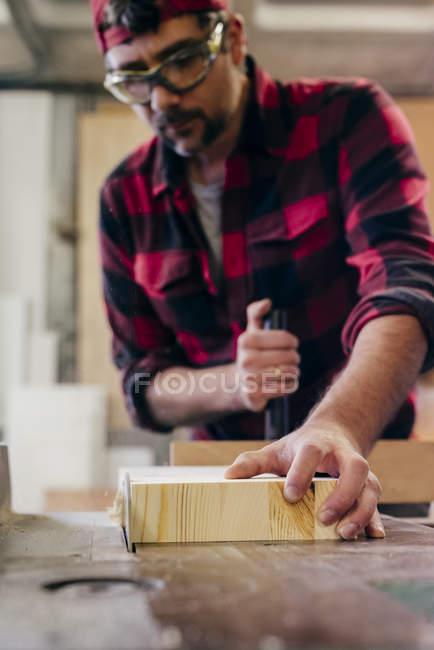 Tischler sägt in Werkstatt mit Motorsäge ein Stück Holz — Stockfoto