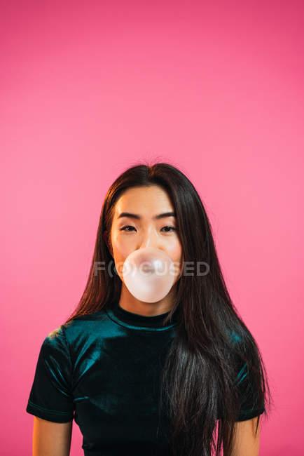Portrait de femme regardant la caméra et soufflant bubble gum sur fond rose. — Photo de stock