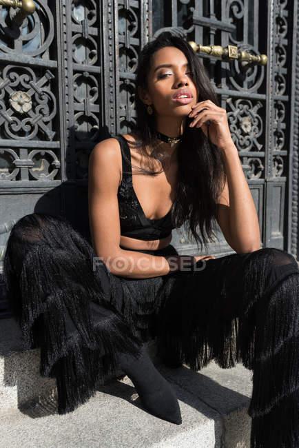 Femme noire élégante posant avec le menton à la main sur les marches — Photo de stock