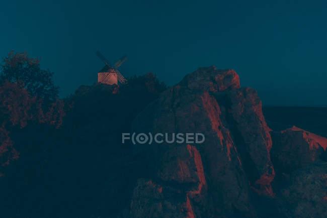 Weißen farbigen Windmühle platziert auf Berg in der Nacht — Stockfoto