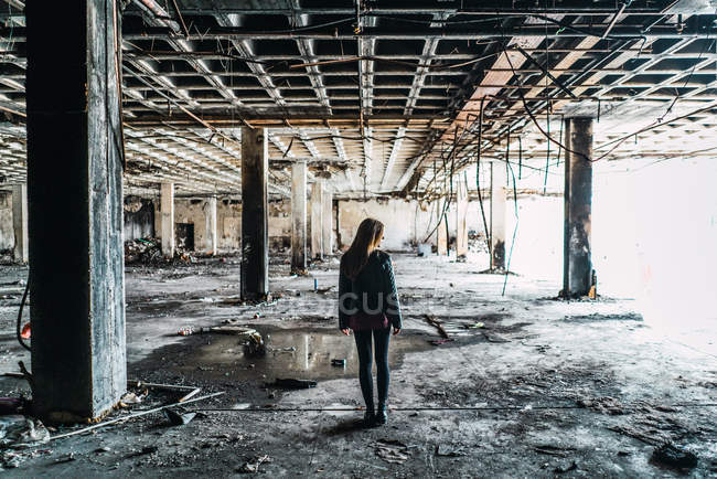 Back view of pretty woman walking in weathered abandoned room. — Stock Photo