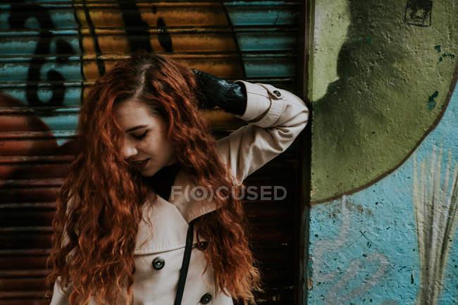 Young redhead woman posing at graffiti wall on city street. — Stock Photo