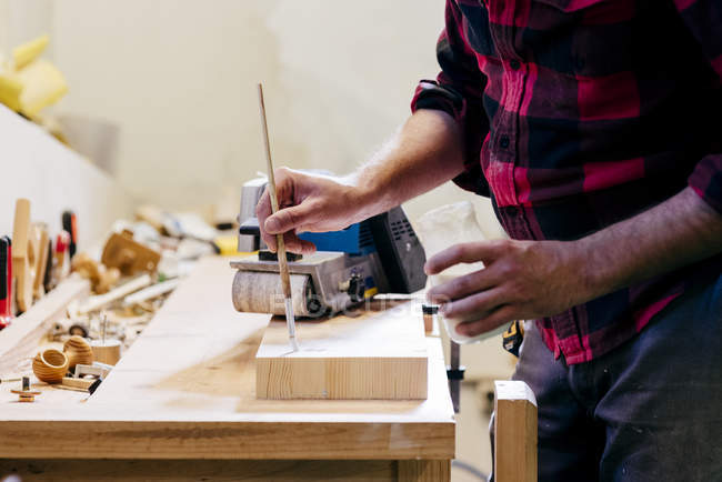 Mid section of carpenter polishing piece of wood at workshop — Stock Photo