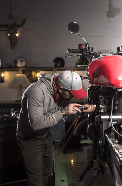 Вид збоку механік в Кап ремонту Користувальницькі мотоцикл на семінарі — стокове фото