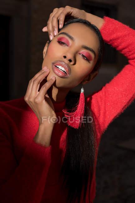 Femme noire sensuelle en vêtements rouges touchant le visage — Photo de stock