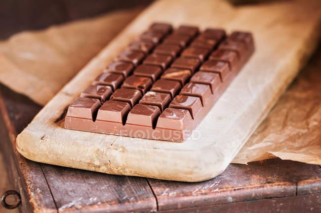 Vue rapprochée de la barre de chocolat noir en planche à découper — Photo de stock