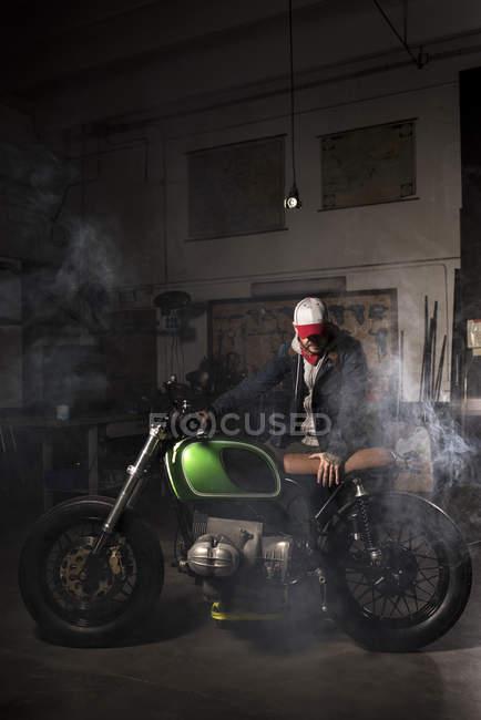 Mechanic actuating custom motorbike at workshop — Stock Photo