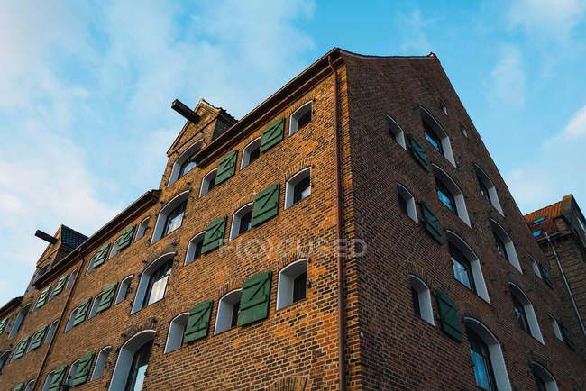 Знизу подання великий цегляний будинок над яскраве небо — стокове фото