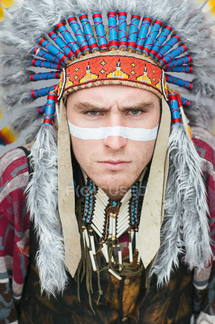Portrait of man with painted line on face posing in traditional Native American costume and looking at camera — Stock Photo