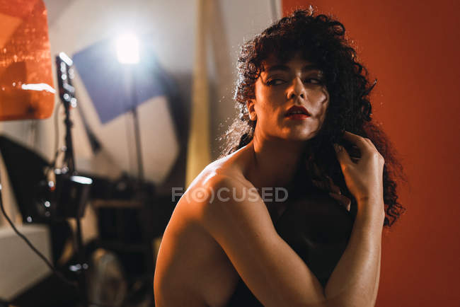 Sensual young curly topless woman posing in studio. — Stock Photo