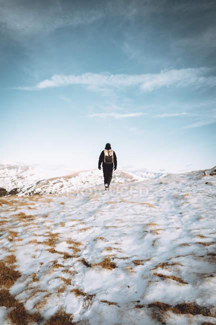 Vista posteriore del turista con lo zaino a piedi su terreni di montagna — Foto stock