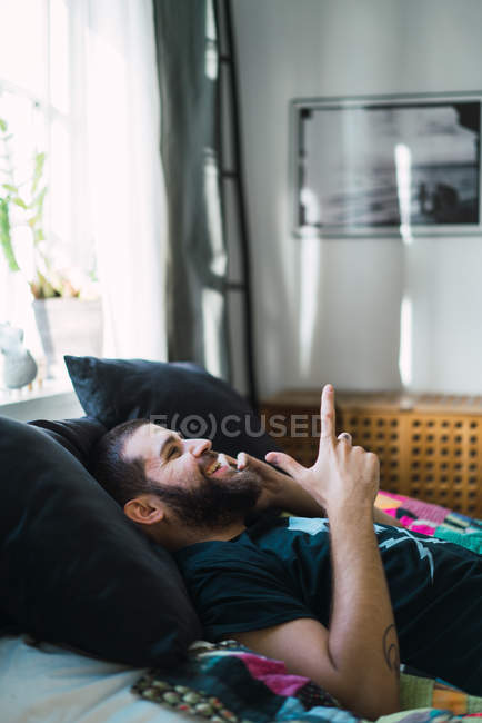 Smiling man lying on sofa at home and talking on phone — Stock Photo