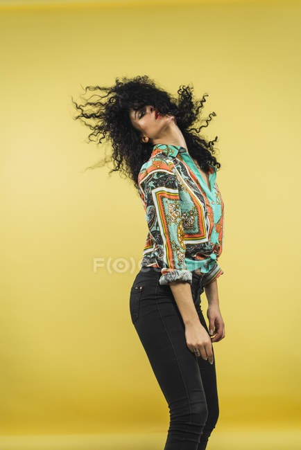 Curly woman waving hair and posing in studio — Stock Photo