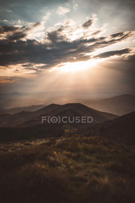 Sunlight penetrating dark clouds over hills landscape — Stock Photo