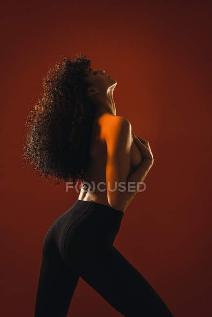 Vista lateral de topless mujer rizada sobre fondo rojo - foto de stock