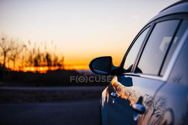 Crop auto parcheggiata sopra il cielo tramonto — Foto stock