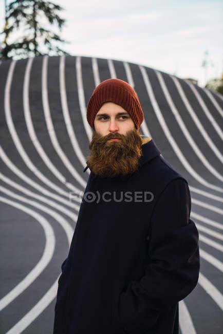 Портрет бородатого мужчины, позирующего на асфальтовом холме — стоковое фото