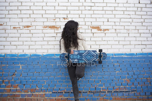 Brunette girl posing with longboard and leaning on brick wall — Stock Photo