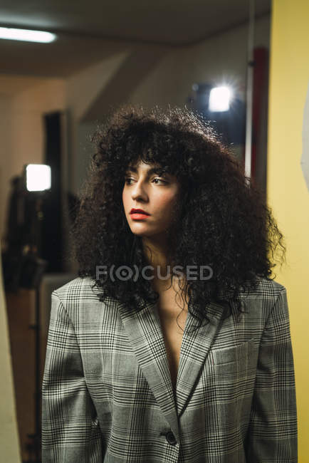 Curly woman in jacket posing at studio — Stock Photo