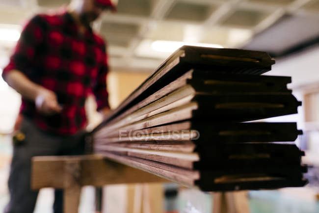 Close up view of stacked wood planks on workbench — Stock Photo