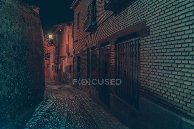 Cena oof iluminado pequeno beco na cidade à noite . — Fotografia de Stock