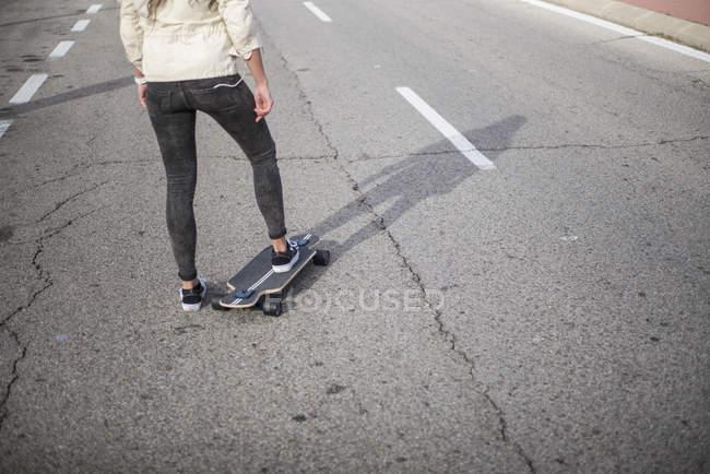 Faible section de fille longboard à cheval sur la route goudronnée urbain — Photo de stock