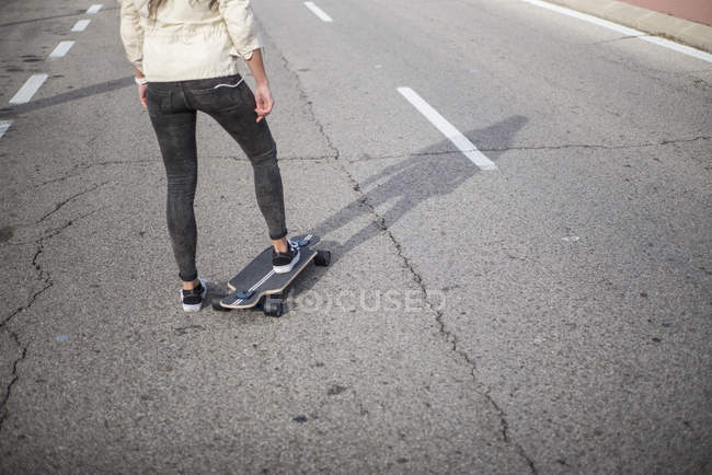 Faible section de fille longboard à cheval sur la route goudronnée urbain — Photo de stock